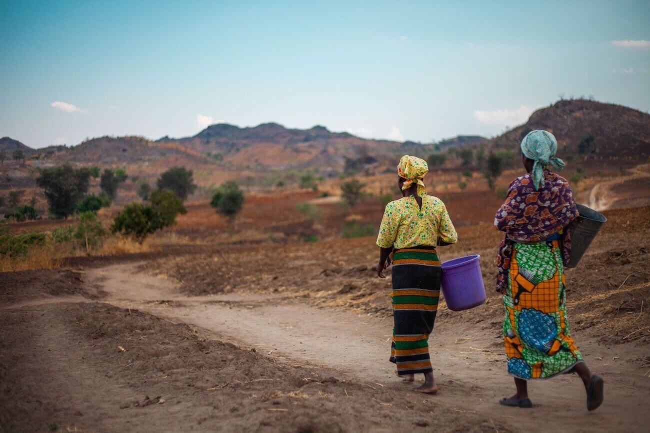 Women in brightly coloured clothes carry water buckets through the Malawian countryside.
